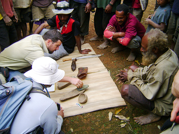 Dr Ben Shaw and some New Guinean locals examine a few of the artefacts unearthed at the Waim dig site in the northern highlands. Picture: UNSW